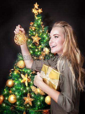 ragazza felice che decorano albero di