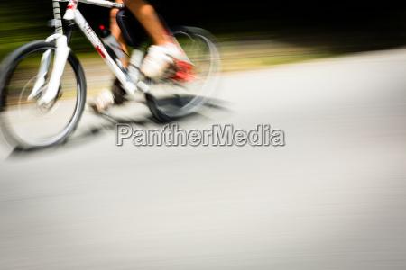 ciclista sfocato strada alberata sfrecciare veloce