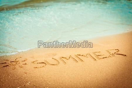 lestate parola scritta nella sabbia su