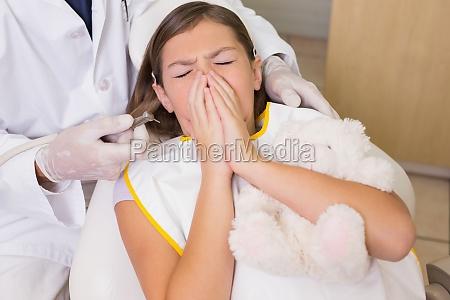dentista pediatrico cercando di vedere starnuti