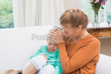madre prendendo la temperatura della figlia