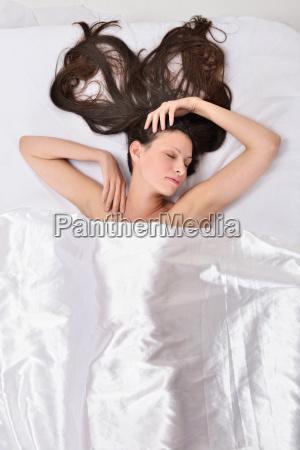 bella donna sul letto sotto lino