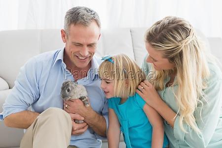 sorridente genitori e figlia seduto con