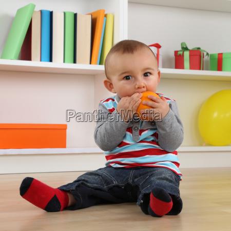 piccolo bambino mangia un frutto arancione