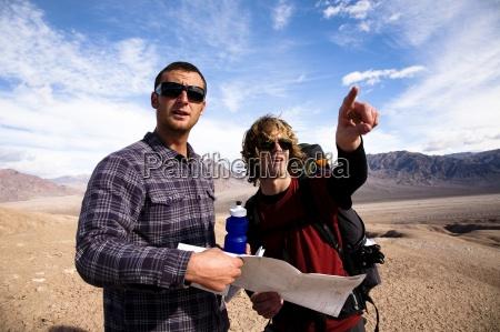 due escursionisti maschi guardano una mappa