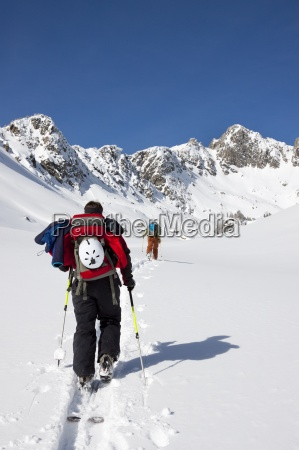 two backcountry skiers skin in the