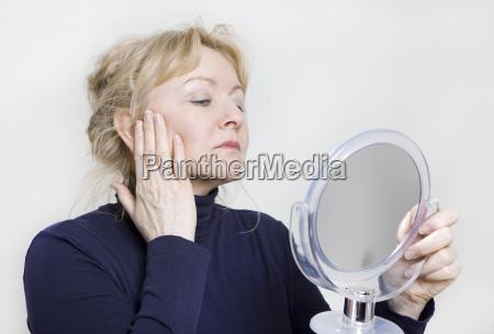 la donna anziana guarda in specchio