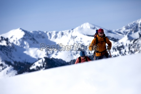 two backcountry skiers hiking over a