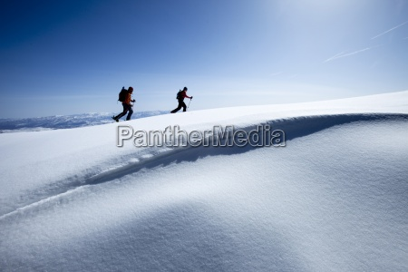 two backcountry skiers hiking in fresh