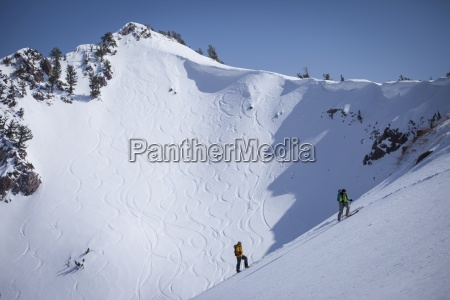 two backcountry skiers hiking up a