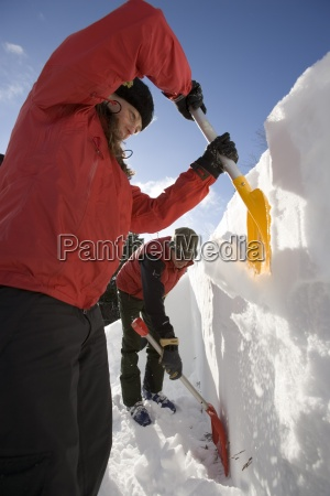 backcountry skiers dig snow pit to
