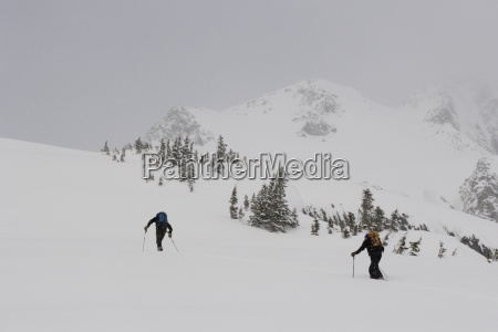 two adults ski tour in mountains