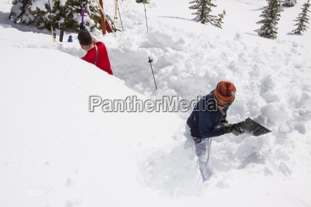 two backcountry skiers dig an avalanche