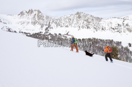 two backcountry skiers skin up hill