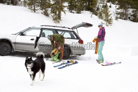 two backcountry skiers put on their