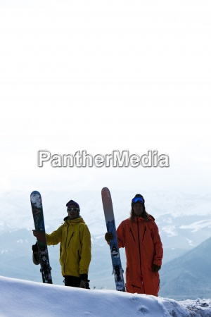 two skiers standing hold their skis