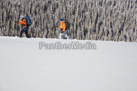two skiers hike along a ridge