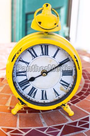 old yellow mechanical alarm clock on