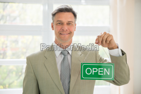 businessman holding open sign