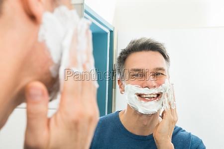 happy man applying shaving cream