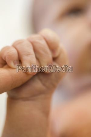 il neonato afferra il dito della