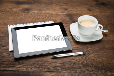 tavoletta digitale e diario con tazza