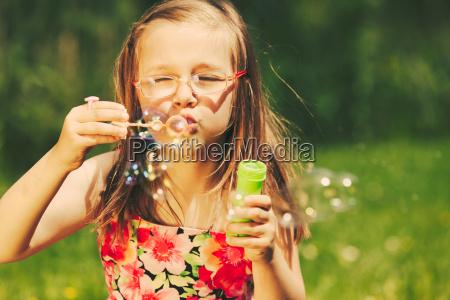 bambino felice bambina che soffia bolle