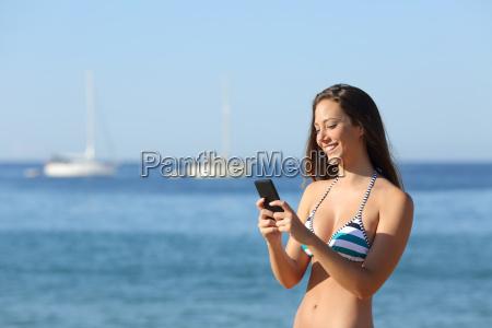 ragazza sunbather mezzo di un telefono
