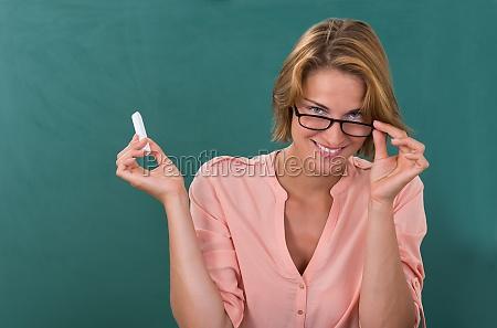 teacher holding chalk against chalkboard