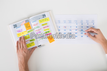 persona mani evidenziazione data sul calendario