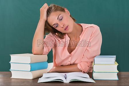 tired female teacher with books