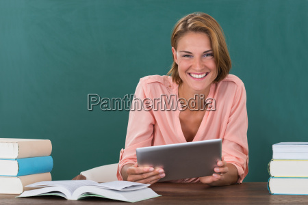 teacher with books and digital tablet