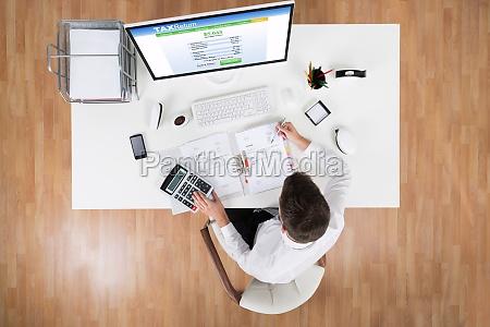 imprenditore calcolare imposta davanti al computer