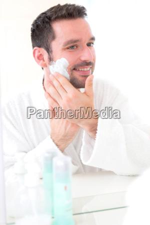 young attractive man shaving his beard