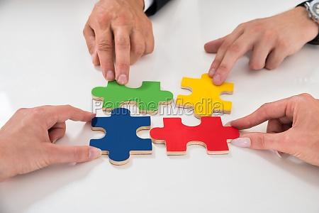 persone che assemblano pezzi di puzzle