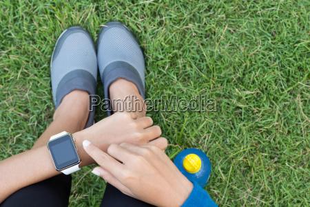 donna atletica utilizzando smartwatch in cima
