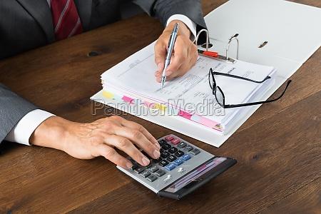 contabile verifica fattura con calcolatrice