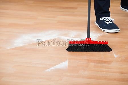 man sweeping hardwood floor