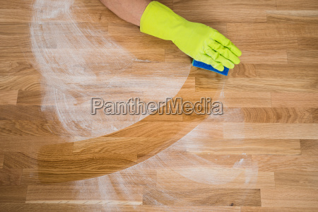 man cleaning dust on wooden table