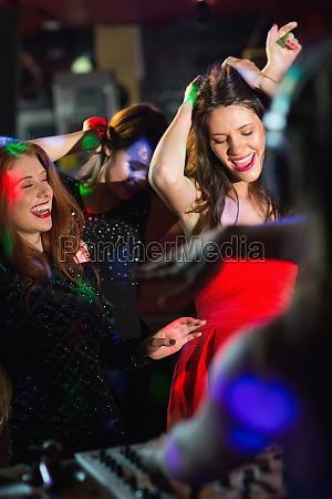 amici felici ballare allo stand dj