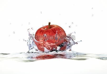 mela rossa spruzzi in acqua vicino