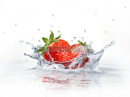 strawberries falling into clear water forming