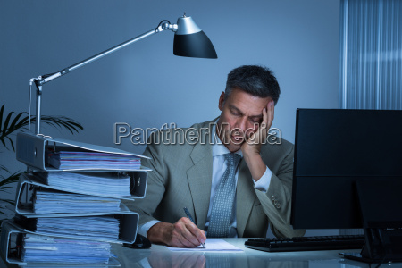 tired businessman writing on document while