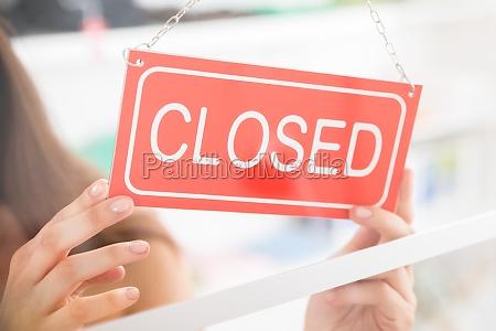 proprietario holding chiuso sign in negozio