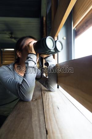donna che usa il binocolo per
