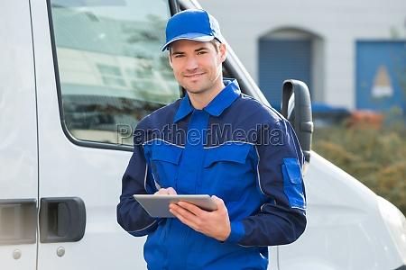 consegna uomo sorridente utilizzando tablet digitale