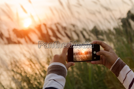 closeup hand using phone taking landscape