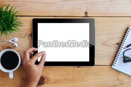 hand using mockup tablet on wood