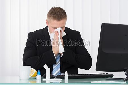 imprenditore malato soffiarsi il naso