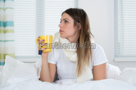 young woman in bed with cup